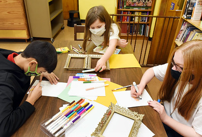 Butler Catholic students (from left) Mateo Saspe, 11, Adelle Crouse, 5,Adison Eicher, 12, work on an art project in preparation for Valentine's Day. Harold Aughton/Butler Eagle.