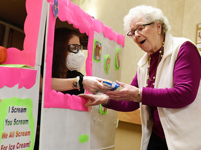 Concordia Activities Assistant, Tiffany Steiner, hands 95-year-old resident, Eleanor Mangus an icecream treat. Concordia maintenance workers made a homemade ice-cream truck from a scooter which comes equipped with music. Harold Aughton/Butler Eagle.