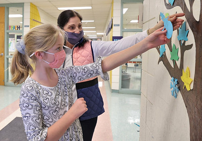 Northwest Elementary third grader Teagan Steyer,9, posts her good deed on the school's Tree of Kindness with her teacher Debbie Grecco Friday. Seb Foltz/Butler Eagle 01/22/21