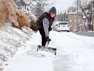Thomas Sheptak, 13, of Butler removes snow from the sidewalks along East Pearl Street Monday morning, February 15, 2021. Harold Aughton/Butler Eagle.