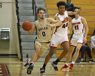 Butler's Raine Gratzmiller drives to the hoop against North Hills' Royce Parham Saturday. Butler held on in the closing seconds for a road win. Seb Foltz/Butler Eagle 02/13/21