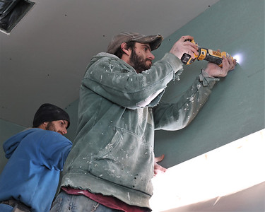 Alan Palmer (right) and Jeff Palmer hang drywall at the Audubon Society of Western nature center under construction at the Monroe Road trailhead of the Butler Freeport Trail in Buffalo Township. Seb Foltz/Butler Eagle 02/16/21