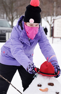 Madisyn McAfee of St Luke Lutheran School places a hat on top of a snowman at the Concordia Lutheran Ministries campus in Cabot. Harold Aughton/Butler Eagle