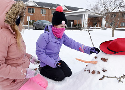 Gabriella Lang and Madisyn McAfee of St. Luke Lutheran School put the final touches on their snowman they built on the campus of Concordia Lutheran Ministries in Cabot on Thursday, February 18, 2021. Harold Aughton/Butler Eagle.