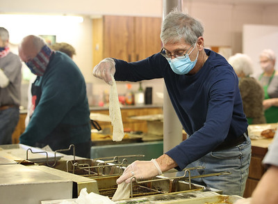 John Harding drops breaded fish filets in the fryer for  St. Louis Roman Catholic Church's  drive-thru fish fry Friday in West Sunbury. Organizers said they sold over 200 dinners that evening. The church will continue serving every Friday through lent. Seb Foltz/Butler Eagle 02/19/21