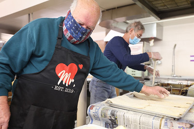 Charles Campbell (left), prepares fish for St. Louis Roman Catholic Church's  drive-thru fish fry Friday in West Sunbury. Organizers said they sold over 200 dinners that evening. The church will continue serving every Friday through lent. Seb Foltz/Butler Eagle 02/19/21