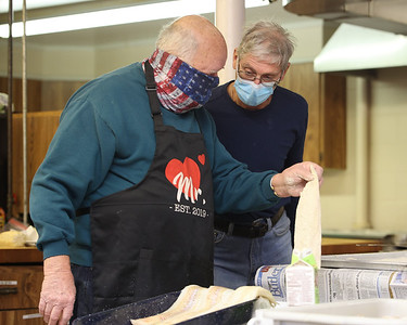 Charles Campbell (left), and John Harding prepare fish for  St. Louis Roman Catholic Church's  drive-thru fish fry Friday in West Sunbury. Organizers said they sold over 200 dinners that evening. The church will continue serving every Friday through lent. Seb Foltz/Butler Eagle 02/19/21