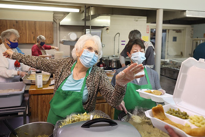 Donna Bryan (left) jokes and points to where Father Adam Verona (not pictured) can find some ketchup during to-go box preparations for St. Louis Roman Catholic Church's drive-thru fish fry Friday. The Church  will continue serving every Friday through lent. Seb Foltz/Butler Eagle 02/19/21