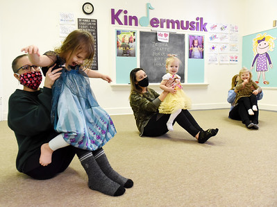 (From left) Annie Pitschman of Butler holds her 3-year-old, daughter, Jacey Pitschman, 3, while Courtney Uhl of Butler holds her daughter, Sawyer Uhl, 2; and Debbie Macadaeg of Cabot holds her granddaughter, Madelyn Moorhead, 2, of Butler during a Kindermusik class at Covenant United Presbyterian Church Wednesday, February 17, 2021. Harold Aughton/Butler Eagle.