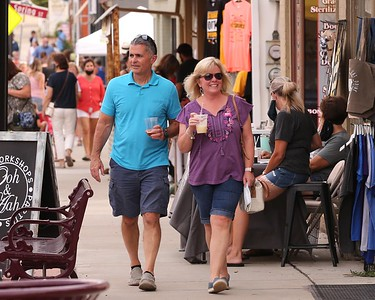Visitors and area residents walk down Main Street during Zelienople's Open Air Market Thursday.  (08/13/20) The Zelienople Area Business Association together with Zelienople Borough began promoting the weekly event as a means to help local restaurants and business in the aftermath of the nation's Covid-19 outbreak. Organizers are promoting CDC guidlines as part of an effort to conduct the event in a safe manner with respect to social distancing recommendations. Seb Foltz/Butler Eagle