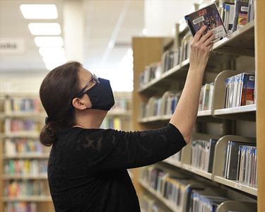 Cranberry Public Library clerk Susan Merten returns cds to the shelf at the library Wednesday. Seb Foltz/Butler Eagle 02/24/21