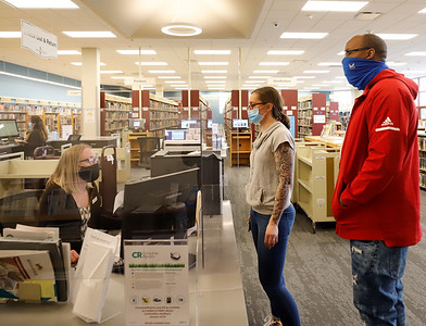 Librarian Rebecca Bess assists Kasey Oberst (center) and Shawn Green at the Cranberry Public Library Tuesday. Seb Foltz/Butler Eagle 02/24/21