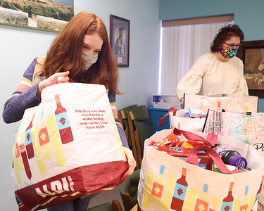 Girl Scout Rachel Blose lifts one of the food bags she organized for her food drive. Seb Foltz/Butler Eagle