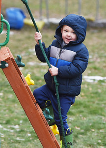 Jackson Karns, 3, of Muddy Creek Township, hangs out on the new swing set that his family won compliments of Lowe's in Butler Wednesday morning, December 30, 2020. Harold Aughton/Butler Eagle