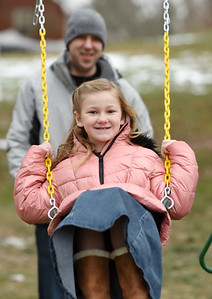 Natalie Karns, 7, of Muddy Creek Township, plays on her new swing set with her father, Matthew Karns Wednesday morning, December 30, 2020. Harold Aughton/Butler Eagle