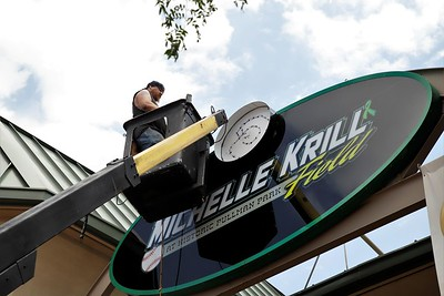 Nathan 'Nate Dog' Watterson puts the finishing touches on the new Michelle Krill Field sign Thursday. The electric sign, with backlit lettering, was designed and built by Butler-based Classic Signs Graphics Garage. Seb Foltz/Butler Eagle