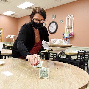 "Server Kimberly Hale cleans a table and collects her tip at Mac's Café Monday morning January 4, 2021.  According to Hale, business was busy, ""nice and steady."" Harold Aughton/Butler Eagle."