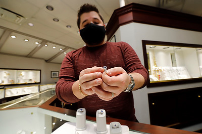 Spencer Mathew of Mathew Jewelers shows a sample wedding ring with a saphire gemstone. Seb Foltz/Butler Eagle 12/29/20