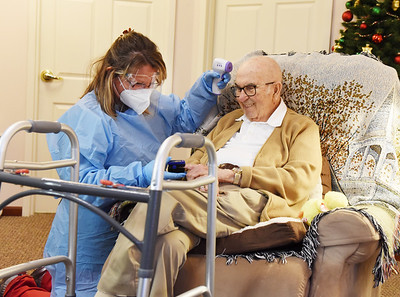LPN Christina Walter of Concordia at the Orchards in Butler checks the temperature of 94-year-old resident Paul Wolfe, Wednesday afternoon, January 6, 2021. According to Administrator Emily Stumpner, Concordia checks resident's temperatures 2- 3 times daily. Harold Aughton/Butler Eagle.