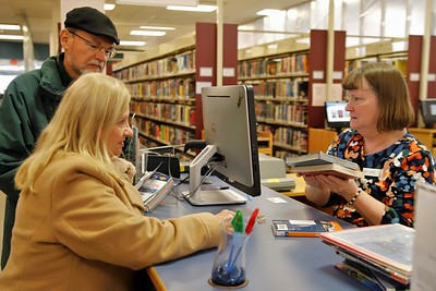 Cranberry Library circulation clerk Barbara Rosenbaum signs out books for Linda and Roger Cwynar of Cranberry. Seb Foltz/Butler Eagle