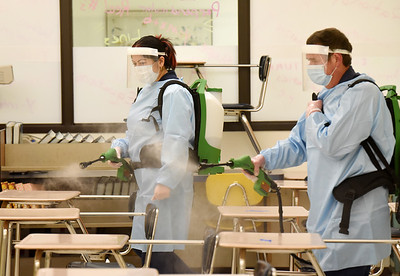 Custodians Viamarie Irigoyen and John Tirk use an electrostatic sprayer to disinfect the classrooms at the Butler Intermediate High School Tuesday, January 12, 2021. Harold Aughton/Butler Eagle.