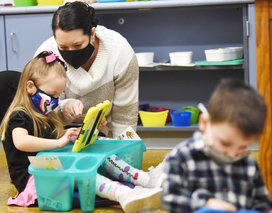 Pre-schooler Emily Edwards, 4, works with teacher Shannon Dorcy during a recent class at Butler Catholic.. The school has launched a technology program in which students use iPads and Chromebooks for remote and in-class instruction. Harold Aughton/Butler Eagle.