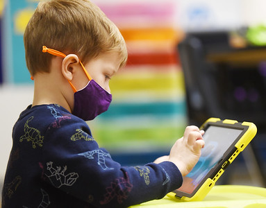 Butler Catholic pre-schooler Conner Hohn, 4, works on learning his ABCs. The school has launched a technology program in which students use iPads and Chromebooks for remote and in-class instruction. Harold Aughton/Butler Eagle.