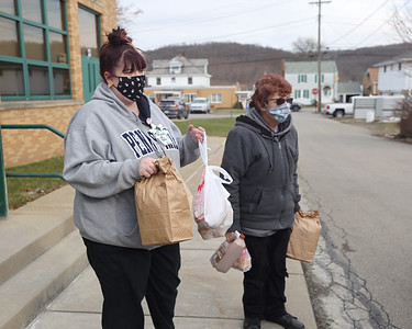 Seneca Valley food service workers Gina Cillo (left) and Nellie Luna wait for a car to pull up to pickup meals at Evans City Middle School Friday during food pickup. Seb Foltz/Butler Eagle 01/15/20