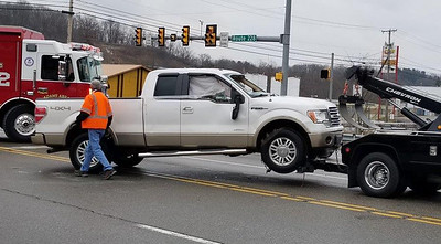 Jim Smith photo. A tow truck hauls away a pickup truck damaged in a two-vehicle crash at Route 228 and Mars-Valencia Road in Adams Township about 12:30 p.m. Sunday. The driver of the pickup and the driver of a car both suffered minor injuries.
