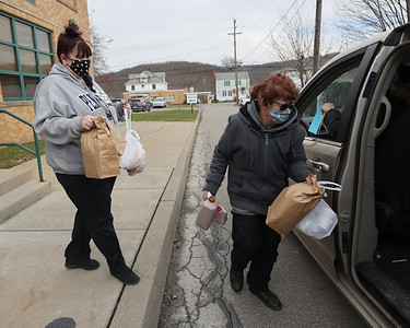 Seneca Valley food service workers Gina Cillo (left) and Nellie Luna deliver meals to a vehicle at Evans City Middle School Friday during food pickup. Seb Foltz/Butler Eagle 01/15/20