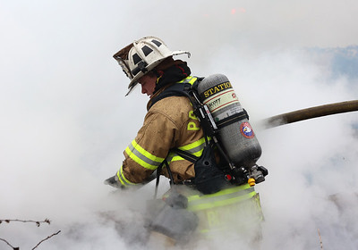 Prospect firefighter Nate Blackwood puts out a hot spot in Tuesday's house fire north of Moraine State Park. Seb Foltz/Butler Eagle