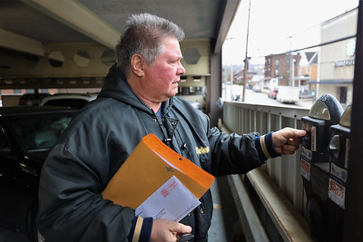 Charles Morrisson of Middlesex feeds a parking meter in the Tier Parking Garage Friday in Butler. Seb Foltz/Butler Eagle 01/22/21