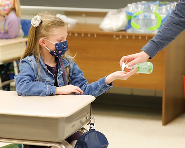 Northwest Elementary first grader Elsie Gerhart gets some hand sanitzer from her teacher, C.J. Gattens, before going up to the Smartboard in class Friday. Seb Foltz/Butler Eagle 01/22/21
