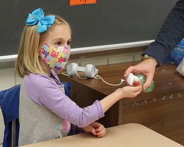 (EDITORS NOTE: NAME COMING) A Northwest Elementary student get's hand sanitizer from her teacher before going up to the Smartboard in class Friday. Seb Foltz/Butler Eagle 01/22/21