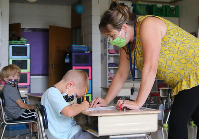 Northwest Elementary School first grade teacher Tanya Collins helps Carter Tosadori with an assignment Tuesday. Seb Foltz/Butler Eagle 09/08/20