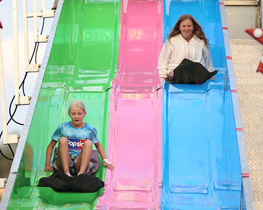 Alexa Agnew,9, (left) and McKaylie Peel,12, ride the amusement park slide at Seven Fields' Community Days fair Thursday night. The annual fair made it's return following a COVID-related hiatus last summer. It runs through Saturday. Seb Foltz/Butler Eagle 07/02/21