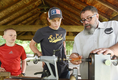 Ben Farrell of Bowls for Good shows Jon and Liam Crowley of Slippery Rock how to sand the wooden barrel of an ink pen at Edco Park in Evans City, Friday. Harold Aughton/Butler Eagle