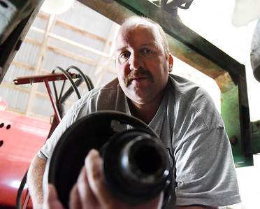 Ed Smith of Smith Farms hooks up the drive shaft of a round bailer to the PTO on a tractor. Harold Aughton/Butler Eagle.