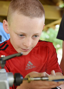 Liam Crowley, 12, of Slippery Rock uses a lathe to make the barrel of a wooden pen at Edco Park in Evans City Friday, July 2, 2021. Harold Aughton/Butler Eagle.