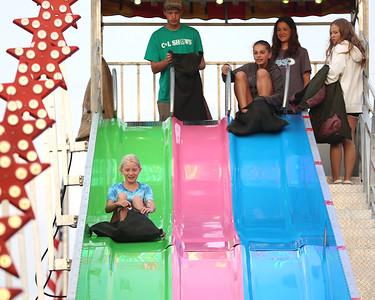 Alexa Agnew,9, (left) gets a head start on Rowan Myers, 12, onthe amusement park slide at Seven Fields' Community Days fair Thursday night. The annual fair made it's return following a COVID-related hiatus last summer. It runs through Saturday. Seb Foltz/Butler Eagle 07/02/21