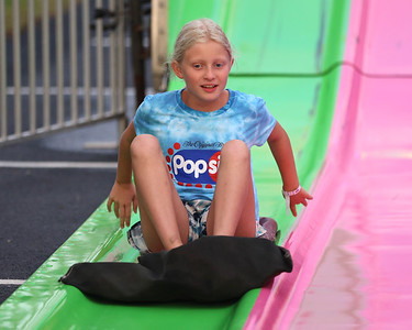 Alexa Agnew,9, comes to a stop at the bottom of the amusement park slide at Seven Fields' Community Days fair Thursday night. The annual fair made it's return following a COVID-related hiatus last summer. It runs through Saturday. Seb Foltz/Butler Eagle 07/02/21