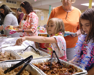 Twins, Piper (left) and Kendall Rose, 8, serve themselves at Trinity Community Presbyterian Church's pig roast Friday. Seb Foltz/Butler Eagle