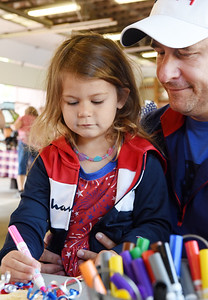 Tim Wach of Middlesex watches as his 4-year-old, daughter, Josie Wach, colors a patriotic craft at the Butler Farmers Market Saturday morning. Harold Aughton/Butler Eagle.