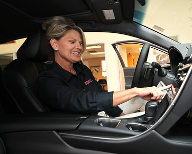 Diehl Toyota sales consultant Amy DeAugustine points to the dash console in a new Toyota Avalon hybrid in Diehl's Route 8 showroom. Seb Foltz/Butler Eagle