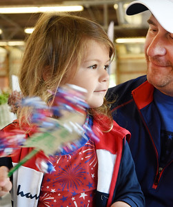Tim Wach of Middlesex watches as his 4-year-old, daughter, Josie Wach, waves a patriotic star she colored at the Butler Farmers Market Saturday morning. Harold Aughton/Butler Eagle.