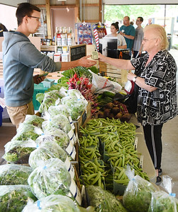 Sandra Miller of Summit Twp. pays Isaac Porter of Pond Hill Farm for a bag of fresh vegetables at the Butler Farmers Marker Saturday morning. Harold Aughton/Butler Eagle.