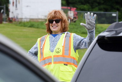 Diane Iman of St. Johns United Church of Christ in Evans City, volunteered directing traffic and distributing food at the Pittsburgh Food Bank distribution held at Lernerville Speedway Tuesday morning. 300 people signed up for the event.    Harold Aughton/Butler Eagle.