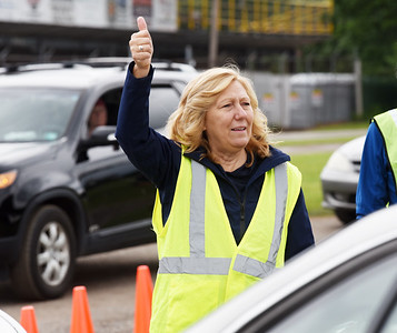 Sue Leinenbach, director of the Butler County Food Bank, gives the all clear to move traffic during the Pittsburgh Food Bank food distribution held at Lernerville Speedway Tuesdy morning. Harold Aughton/Butler Eagle.