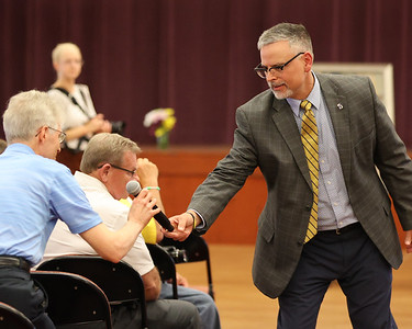 Butler County Community College president Nick Neupauer hands off a microphone to a guest at Wednesday's celebration of life for longtime college donor Bob Heaton. Heaton died in January. Family friends and college staff shared memories during the commemoration. Seb Foltz/Butler Eagle