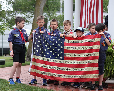 Members of Zelienople/Cranberry area Cub Scout Pack 457 hold up a flag with the words to the pledge of allegience during the finale for the Zelienople Historical Society's Patriotic Porch Tour week celebration at the Passavant House. Seb Foltz/Butler Eagle 07/08/21